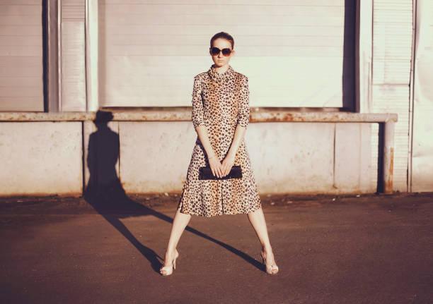 modisch selbstbewusste frau im kleid mit leoparden print, weibliche modell hält handtasche kupplung posiert abend wirft einen schatten auf die stadt straße hintergrund - vogue muster stock-fotos und bilder