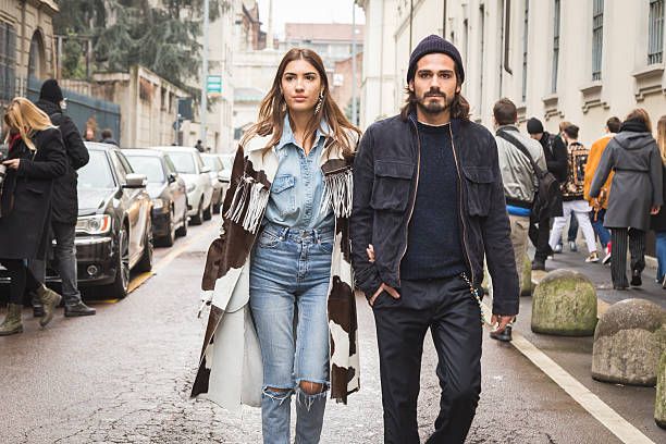 Fashionable couple at Milan Fashion Week Milan, Italy - February 27, 2016: Fashionable couple walks outside Ermanno Scervino fashion show during Milan Women's Fashion Week. editorial stock pictures, royalty-free photos & images