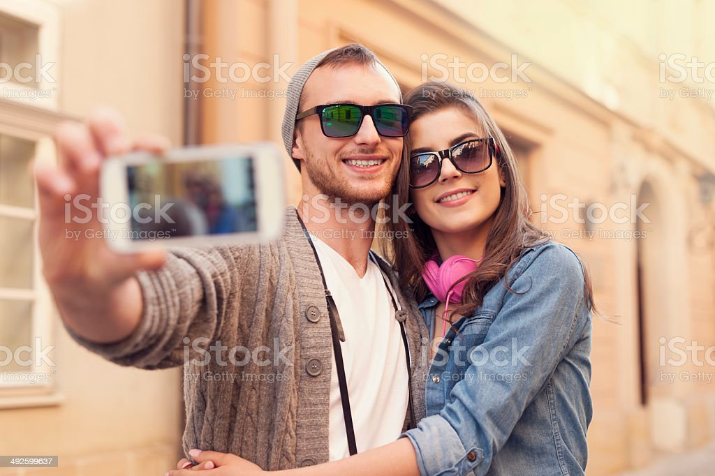Fashionable couple taking selfie by mobile phone stock photo