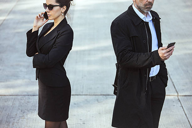 fashionable couple using mobile phones outdoor. - detachment stock pictures, royalty-free photos & images