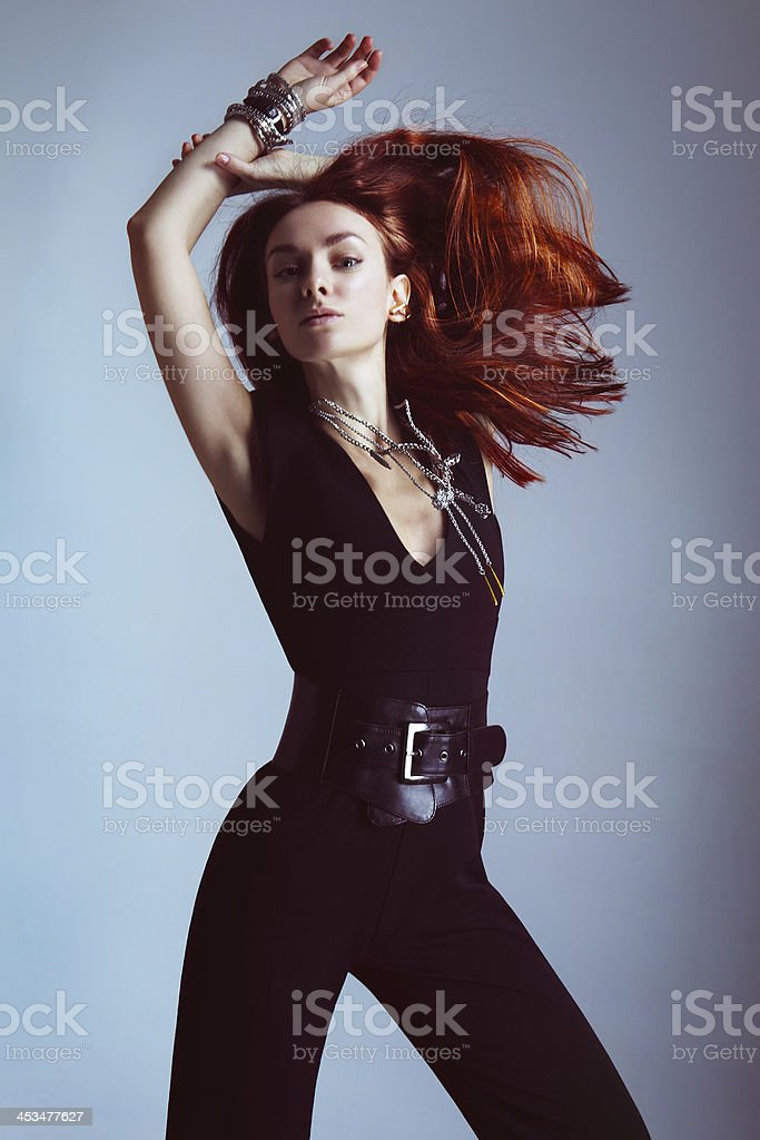 Fashionable dancing woman in black jumpsuit stock photo