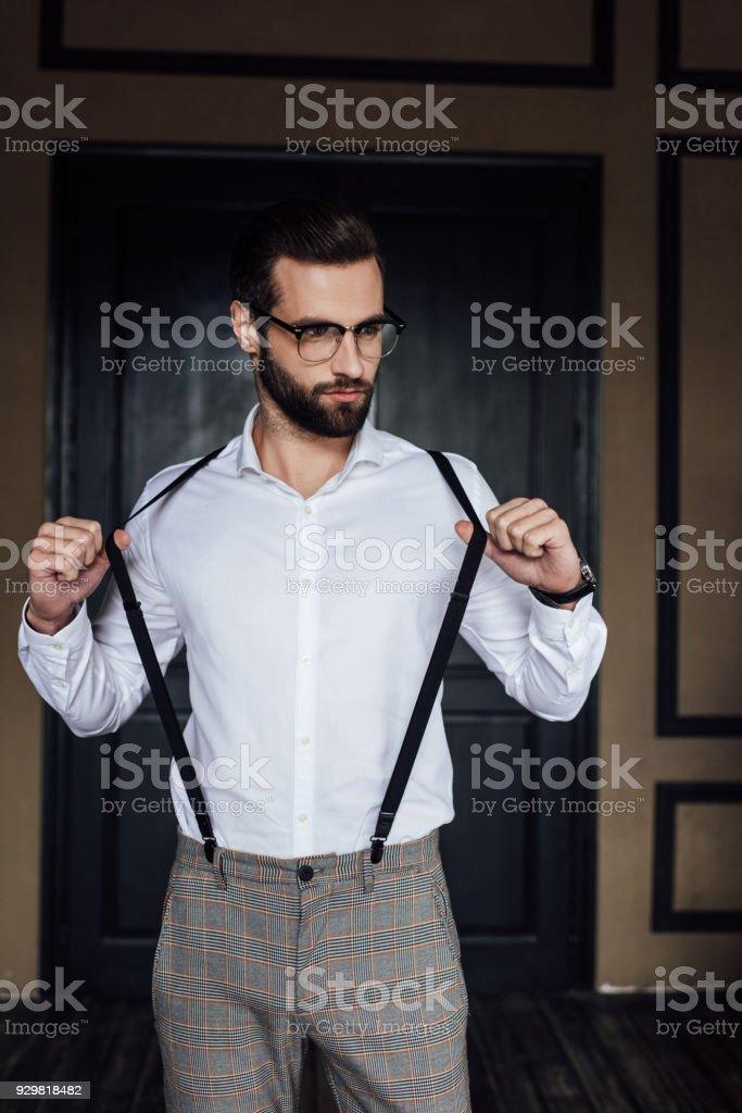 la mode homme élégant posant en chemise blanche et bretelles contre porte intérieur loft - Photo