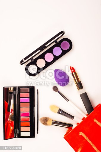 istock Fashionable female accessories brushes smartphone lipstick eyeshadow and red bag. 1127709429