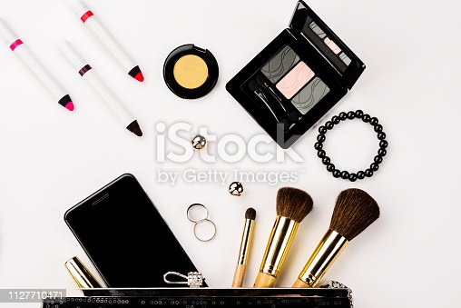 847905020 istock photo Fashionable female accessories brushes smartphone lipstick eyeshadow and black bag. 1127710471