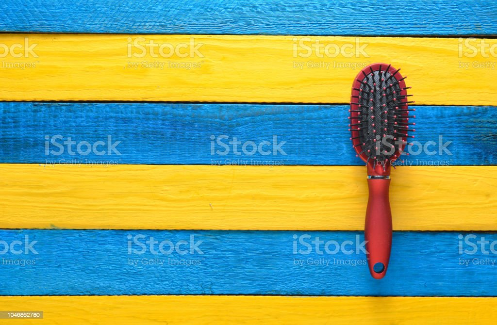 Fashionable female comb for hair care on a yellow blue wooden table. Trend of minimalism. Copy space. Top view. Summer concept. стоковое фото