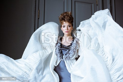 506798692istockphoto Fashionable female portrait of cute lady in dress indoors 959772040