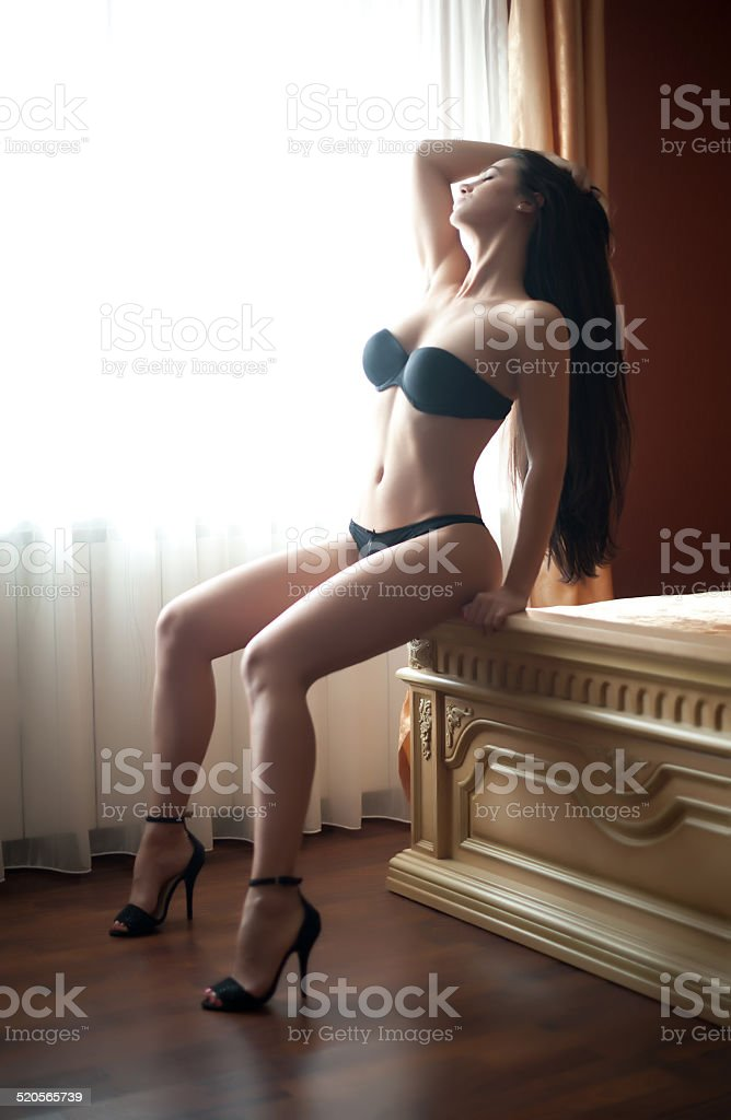 Fashionable female with attractive body posing provocatively stock photo