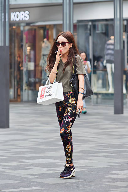 modische mädchen in peking einkaufsviertel rauchen zigarette, gehen. - nike damen sneaker stock-fotos und bilder