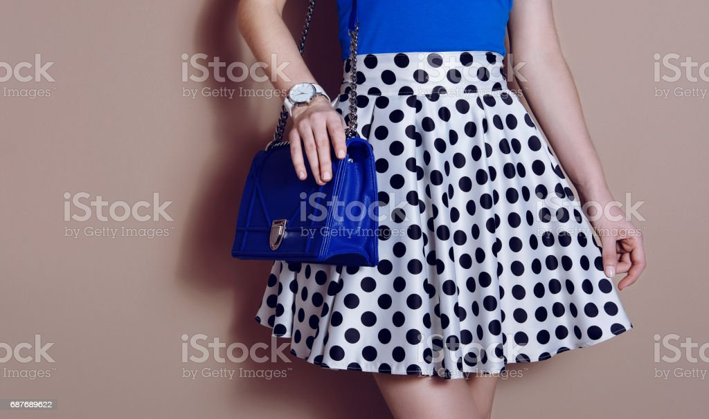 Fashionable girl in polka dots dress with blue bag. Close up stock photo