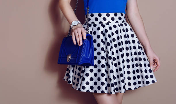 fashionable girl in polka dots dress with blue bag. close up - skirt stock photos and pictures
