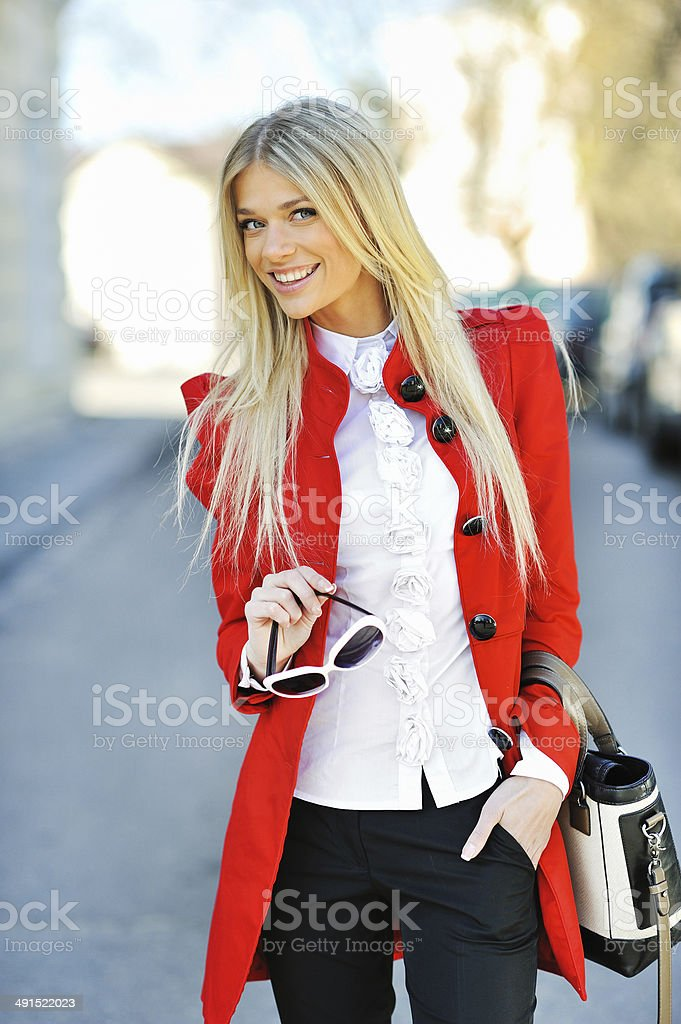 Fashionable girl in red dress with bag stock photo