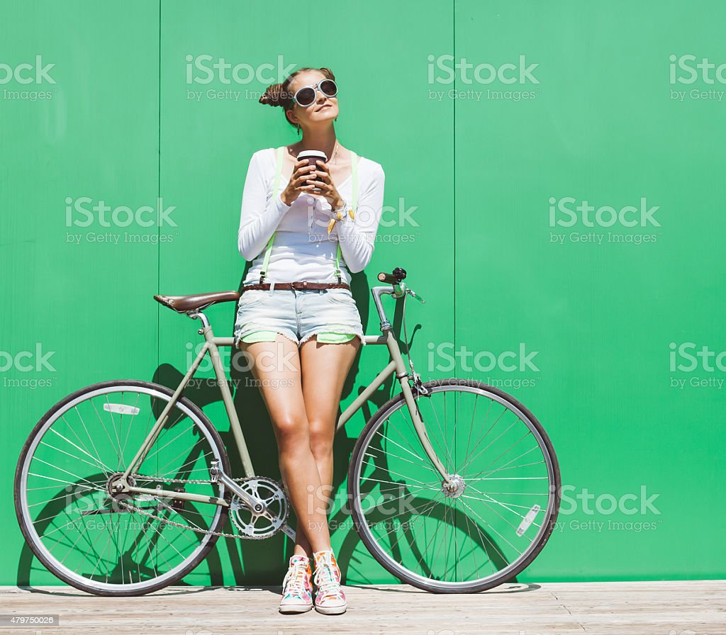 Fashionable girl in shorts stands with  bicycle fix gear stock photo