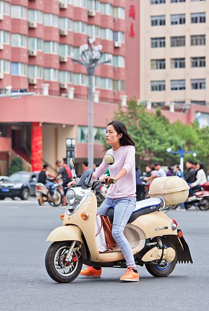 modische mädchen in einem gelben retro-design e-bike, kunming, china - nike damen sneaker stock-fotos und bilder