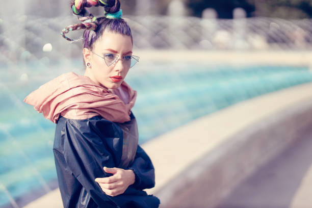 Fashionable girl on street with artesian fountain in background. Extreme fashion stock photo