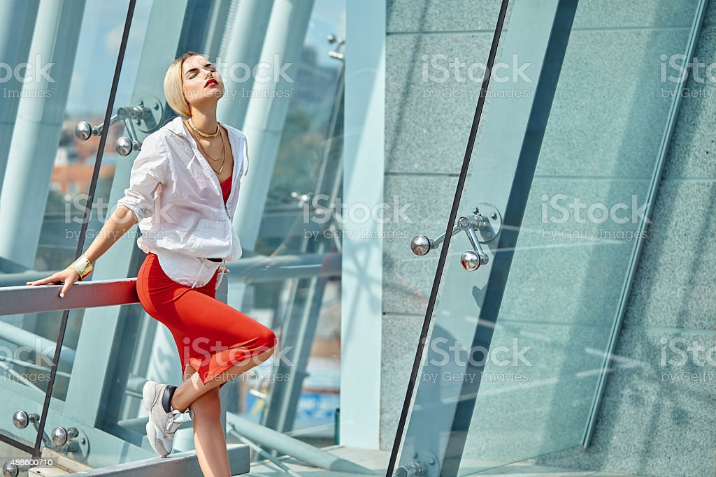 Fashionable girl standing in red skirt and white windcheater stock photo