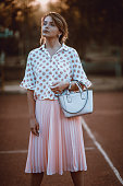 Fashionable Girl Standing On Tennis Court During Sunset