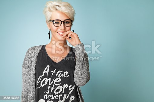 Fashionable girl with glasses and short hair and dressed in a gray T-shirt, standing on the blue background