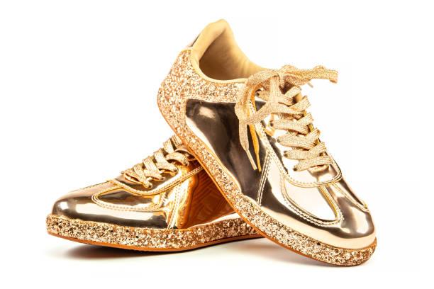 Fashionable golden sneakers in metallic design stock photo