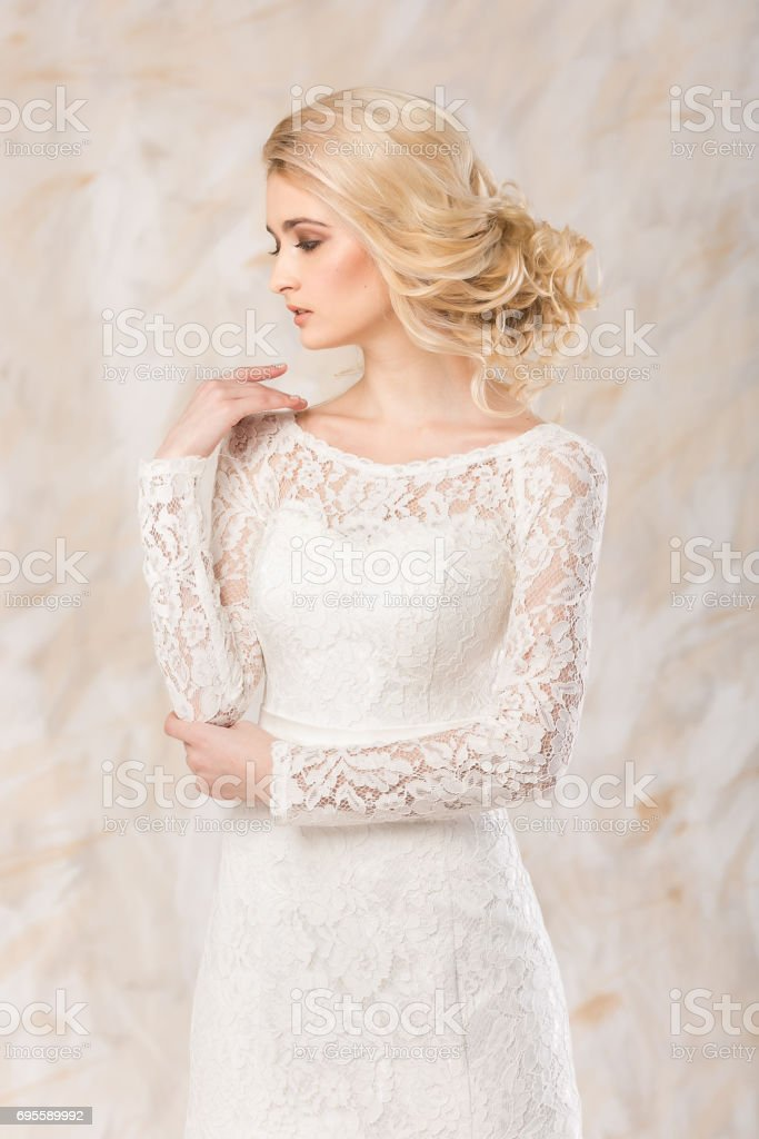 fashionable gown, beautiful blonde model, bride hairstyle and makeup concept - young exciting lady in white wedding festive dress, standing indoors on light background, romantic slender woman posing stock photo