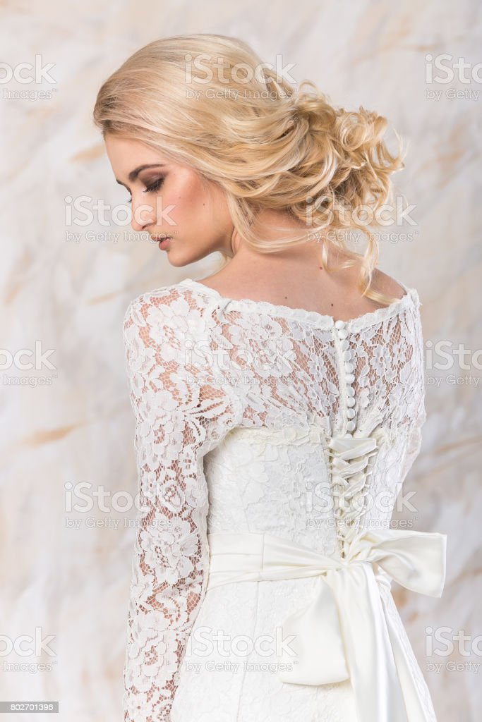 fashionable gown, beautiful blonde model, bride hairstyle and makeup concept - young romantic lady in white wedding dress, pretty slender woman stand indoors on light background, back view stock photo