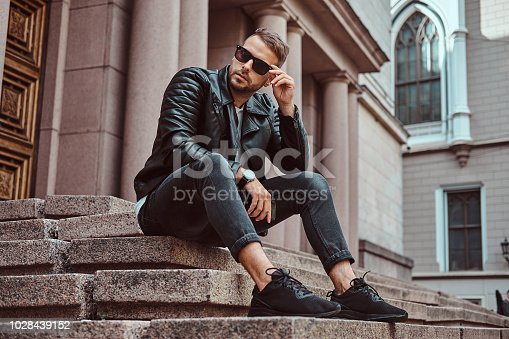 Fashionable guy dressed in a black jacket and jeans holds a smartphone sitting on steps against an old building in Europe.