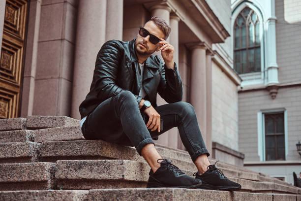 유행 남자 검은 자 켓에 입고와 청바지 유럽에는 오래 된 건물에 대 한 단계에 앉아 스마트폰 보유. - 우아 뉴스 사진 이미지
