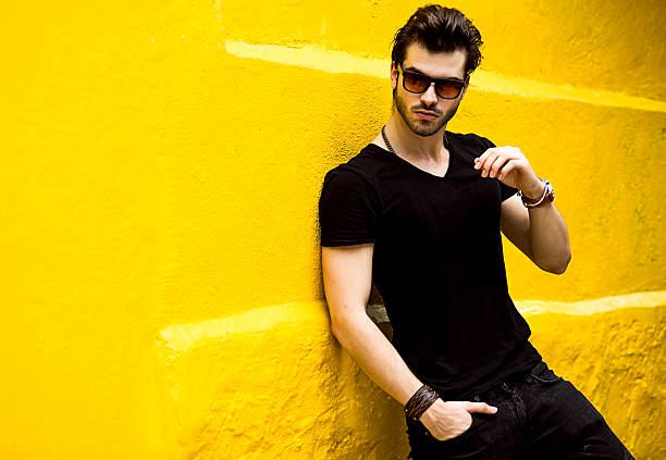 fashionable handsome man isolated on yellow wall stock photo