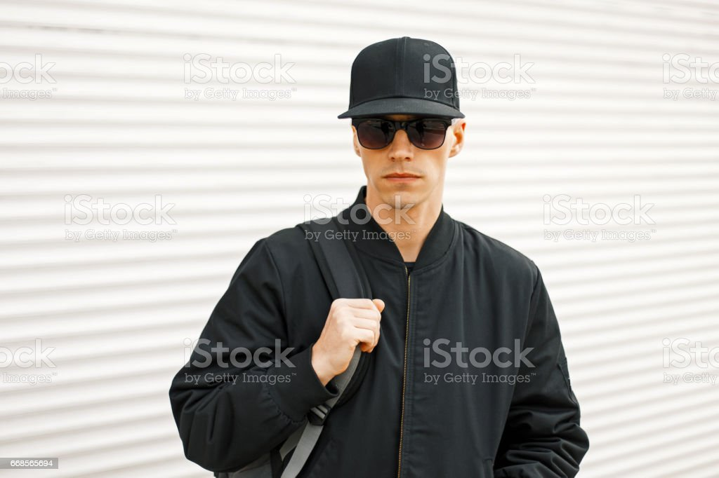 Fashionable handsome man with black glasses with black modern clothes near the white wall stock photo