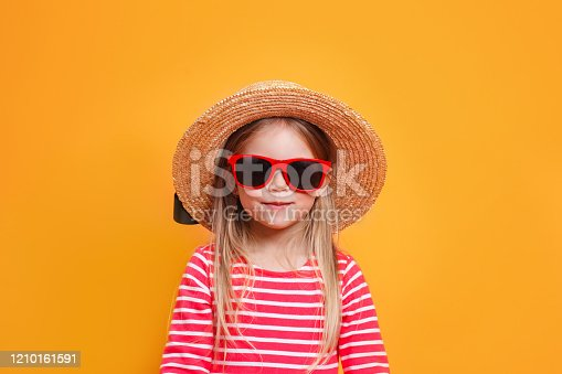 604367022 istock photo Fashionable little girl wearing a straw hat and sunglasses on yellow background 1210161591