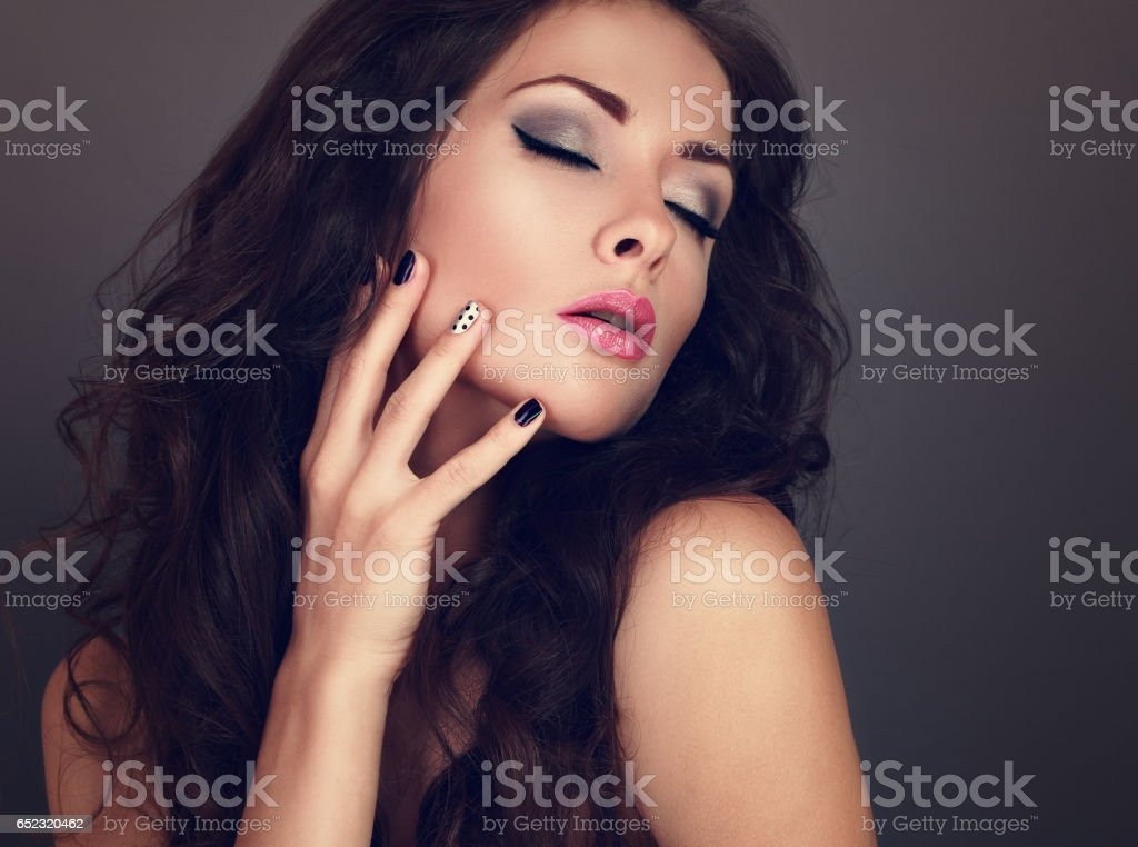 Fashionable makeup woman with long curly hair, closed eyes, creative manicured nails and grey eyeshadow on grey background. Closeup toned portrait. Perfect eyebrow and pink lipstick stock photo