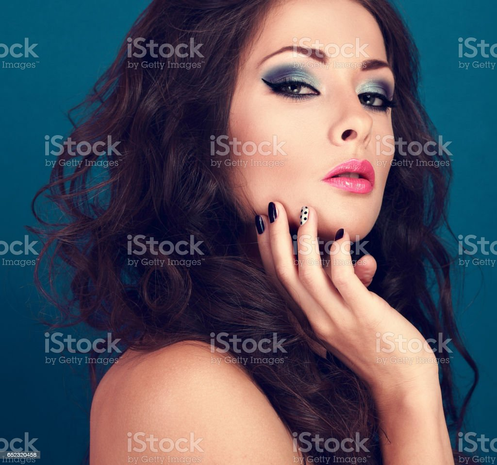 Fashionable makeup woman with long curly volume hair and creative manicured nails on blue background. Closeup. Perfect eyebrow and pink lips stock photo
