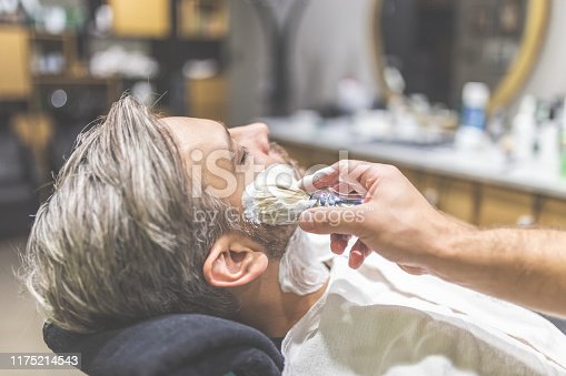 483333652 istock photo Fashionable man client during beard shaving in barber shop. 1175214543
