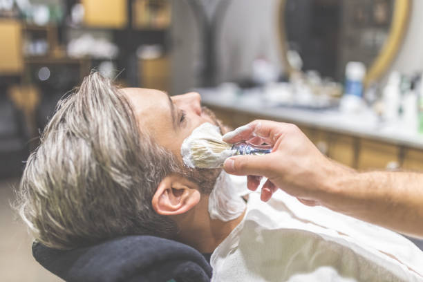 Fashionable man client during beard shaving in barber shop. Professional hairdresser applying shaving foam on client skin in barbershop. shaving brush shaving cream razor old fashioned stock pictures, royalty-free photos & images