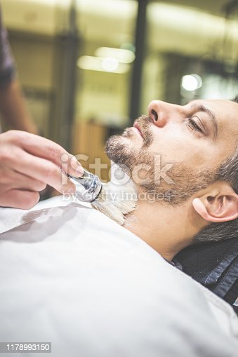 483333652 istock photo Fashionable man client during beard shaving in barber shop. 1178993150