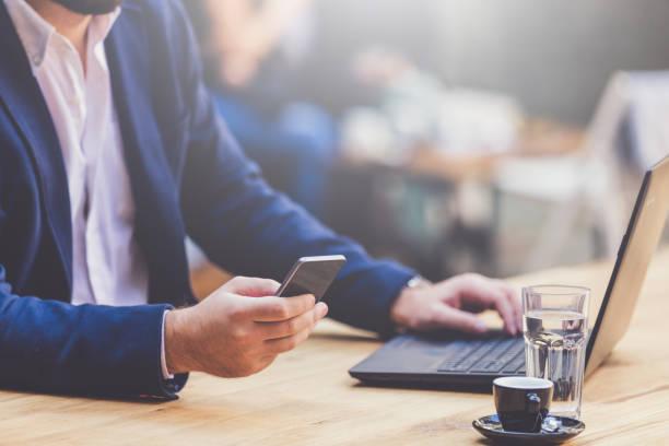 ファッショナブルな男のコーヒー ショップでノート パソコンのキーボード上の手で携帯電話を保持しています。 ストックフォト