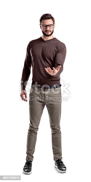 A fashionable man in glasses and casual clothes stands looking at his empty upturned hand as if holding an object. Presentation. New product. Holding out sample.