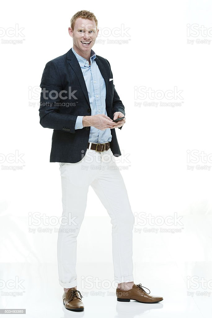 Fashionable man looking at camera & holding mobile stock photo