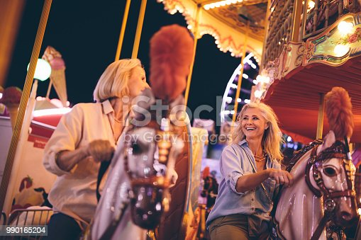 Happy senior women on summer vacations enjoying travelling carnival merry-go-round ride and laughing together