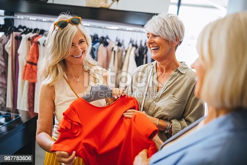 Smiling senior friends having fun shopping for fashionable clothes together in clothes shop