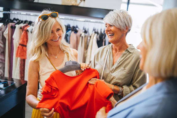 Fashionable mature women shopping for clothes in fashion boutique stock photo