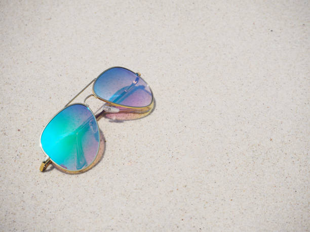048778c525 Fashionable mirror sunglasses on sand beach background stock photo