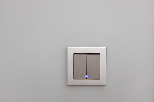 Fashionable modern silver light switches on a gray wall, opposite view. Switch with night illumination. Concept interior details, electrical equipment, device. Horizontal.