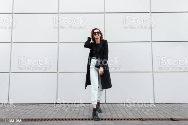 Fashionable modern young hipster woman in stylish clothes in leather shoes with a handbag in stylish sunglasses is standing and smiling near the modern building in the city. European beautiful girl. Fashionable modern young hipster woman in stylish clothes in leather shoes with a handbag in stylish sunglasses is standing and smiling near the modern building in the city. European beautiful girl. Adult Stock Photo