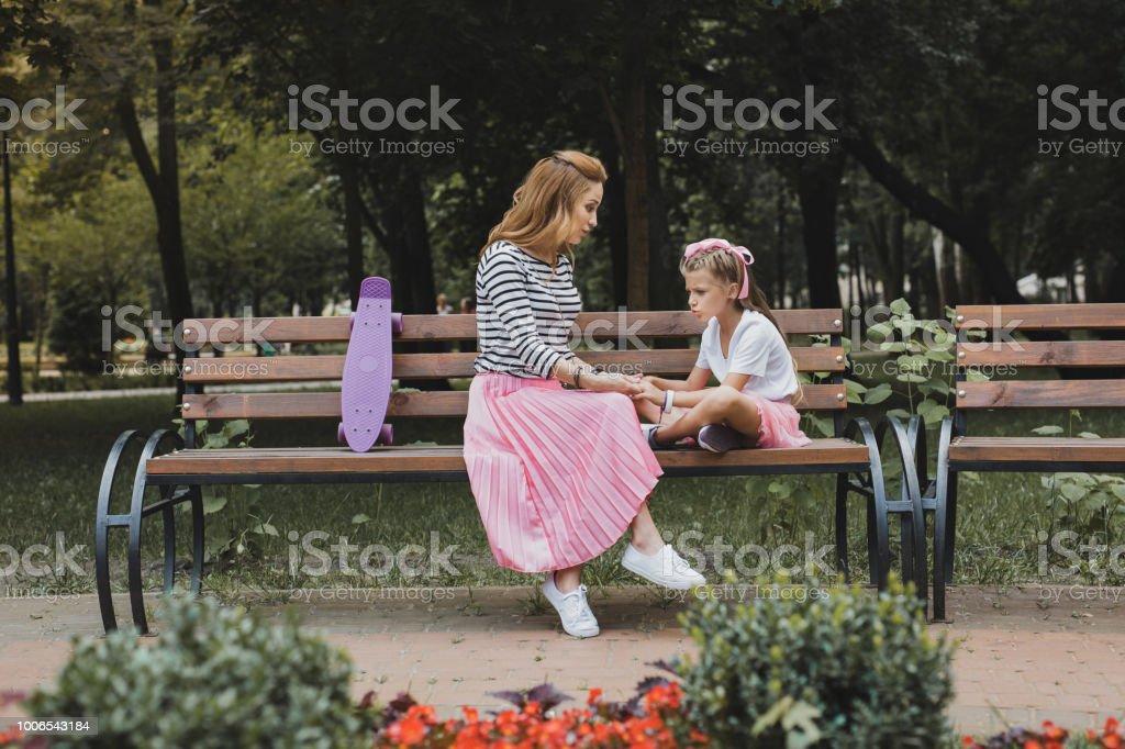 Modische Mutter sitzt auf der Bank im Park in der Nähe ihrer Tochter – Foto