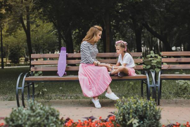 modische mutter sitzt auf der bank im park in der nähe ihrer tochter - lange gestreifte röcke stock-fotos und bilder