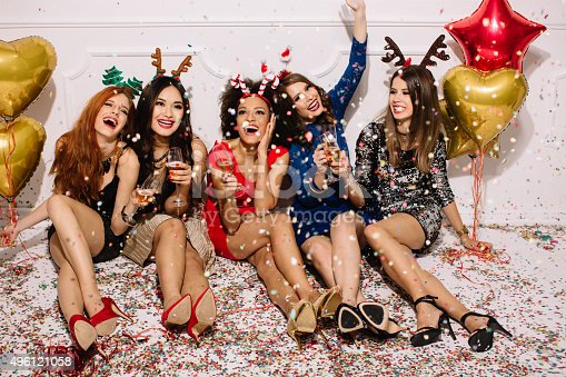 Group of beautiful young girls celebrating New Year. Sitting in front of a white wall, cheering with champagne and laughing. Confetti on the floor. Wear elegant dresses. Room is decorated with star and heart  shaped balloons.