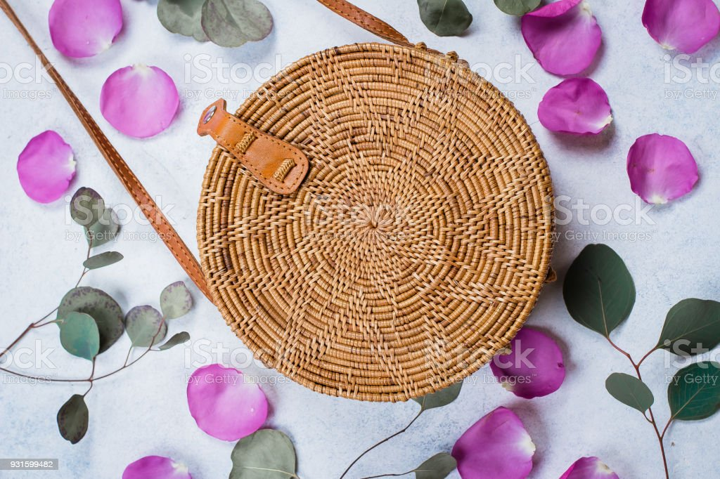Fashionable rattan bag, flowers rose petals and eucalyptus leaves on light background. Copy space, top view stock photo