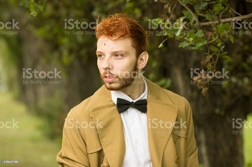 Fashionable red haired model posing in park, close up. stock photo