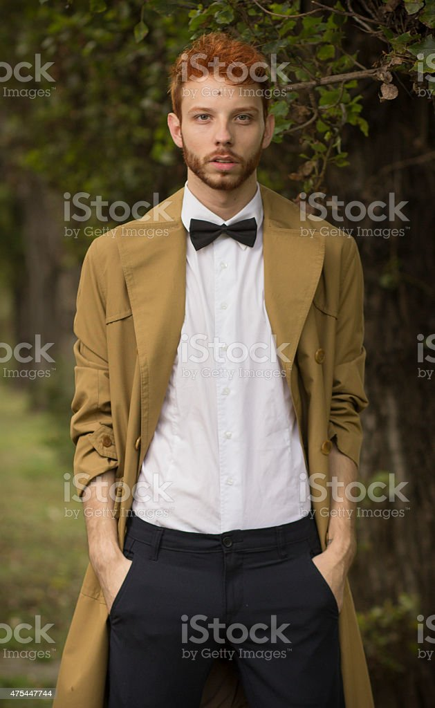 Fashionable red haired model posing in park stock photo