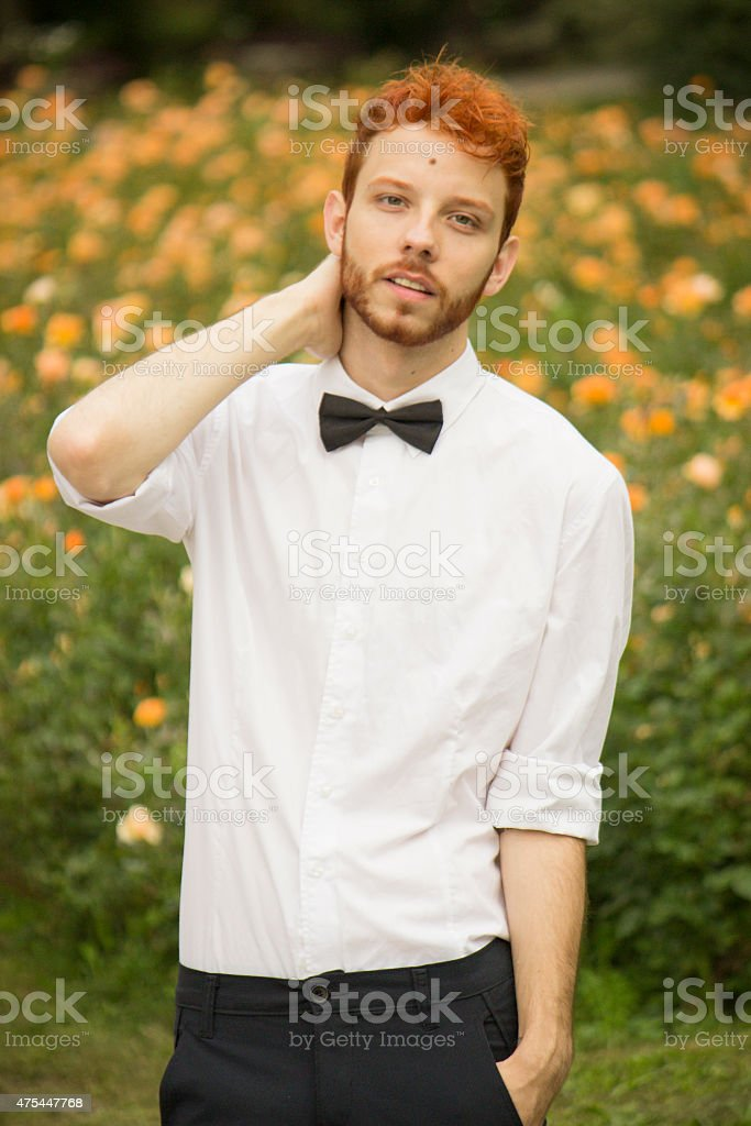 Fashionable red haired model posing in park, upper body shot. stock photo